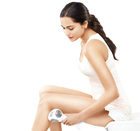 Woman treating her legs with the Tria Beauty Hair Removal Laser 4X